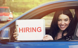 Happy woman sitting inside car showing white card with hiring sign message. Happy woman sitting inside new car showing white card with hiring sign message on a Royalty Free Stock Photos