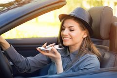 Happy woman sitting inside convertible car using a smart phone voice recognition function on line. Outdoors on a back lit park background royalty free stock photography
