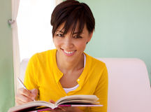 Happy woman sitting inside writing in a journal. Stock Images