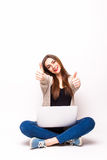 Happy woman sitting with laptop showing thumb up signs Stock Image