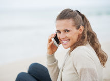 Happy woman sitting on lonely beach and talking cell phone Stock Image