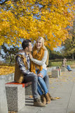 Happy woman sitting on man's lap at park during autumn Stock Image