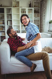 Happy woman sitting on mans lap in living room Stock Photo