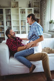 Happy woman sitting on mans lap in living room Stock Photos