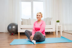 Happy woman sitting on mat at home Royalty Free Stock Image