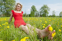 Happy woman sitting in a meadow Stock Image