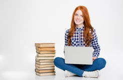 Happy woman sitting near stack of books and using laptop Royalty Free Stock Photos