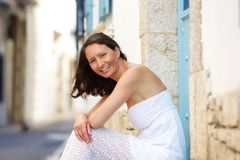 Happy woman sitting outside in summer dress Royalty Free Stock Photography