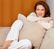 Happy woman sitting with pillow on couch Royalty Free Stock Photography