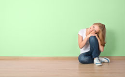 Happy  woman is sitting in a room with a blank wall Stock Images