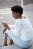 Happy woman sitting and sending text message on cellphone Stock Image
