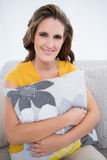 Happy woman sitting on sofa holding pillow Royalty Free Stock Photography
