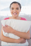 Happy woman sitting on sofa holding pillow Royalty Free Stock Photo