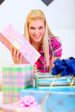 Happy woman sitting on sofa and holding present Stock Photo