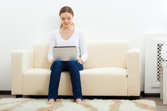 Happy woman sitting on sofa with laptop Stock Photography