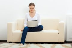 Happy woman sitting on sofa with laptop Stock Image