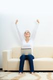 Happy woman sitting on sofa with laptop Royalty Free Stock Photo