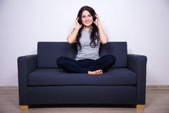 Happy woman sitting on sofa and listening music with headphones Stock Image