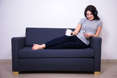 Happy woman sitting on sofa, listening music with mobile phone a Stock Photo