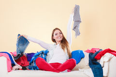 Happy woman sitting on sofa in messy room at home. Stock Images