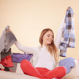 Happy woman sitting on sofa in messy room at home. Royalty Free Stock Image