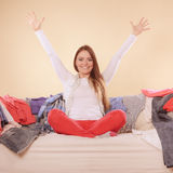Happy woman sitting on sofa in messy room at home. Royalty Free Stock Images