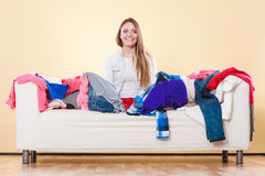 Happy woman sitting on sofa in messy room at home. Stock Photography