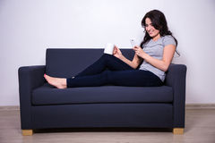 Happy woman sitting on sofa with mobile phone and mug of tea Royalty Free Stock Photos