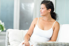 Happy woman sitting on sofa Royalty Free Stock Photography