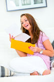 Happy woman sitting on sofa and reading letter Stock Image