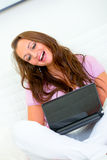 Happy woman sitting on sofa and using laptop Royalty Free Stock Photo