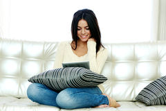 Happy woman sitting on the sofa and using tablet computer Stock Photo