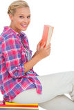 Happy woman sitting on a stack of books and holding a book Royalty Free Stock Photography