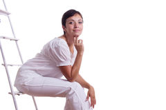 Happy woman sitting on step ladder Stock Images