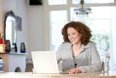 Happy woman sitting at table at home looking at laptop Royalty Free Stock Photos
