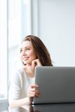 Happy woman sitting at the table with laptop computer Royalty Free Stock Photos