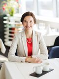 Happy woman sitting at table in restaurant Stock Photos