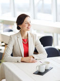 Happy woman sitting at table in restaurant Royalty Free Stock Images