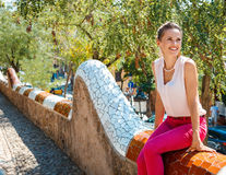 Happy woman sitting on trencadis style fence and looking aside Stock Photos