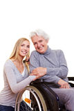 Happy woman sitting in wheelchair. With young nurse to her side Royalty Free Stock Photos
