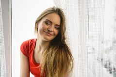 Happy woman sitting on windowsill, energizing morning. Thinking about day, relaxing having good time Stock Image