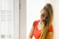 Happy woman sitting on windowsill, energizing morning. Thinking about day, relaxing having good time Stock Photography