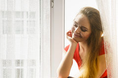 Happy woman sitting on windowsill, energizing morning. Thinking about day, relaxing having good time Royalty Free Stock Photos