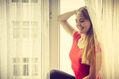 Happy woman sitting on windowsill, energizing morning. Thinking about day, relaxing having good time Royalty Free Stock Photography