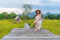 Woman sitting on wooden bridge with yellow cosmos flower field royalty free stock photo