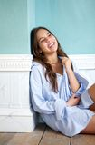 Happy woman sitting on wooden floor and laughing at home Stock Photos