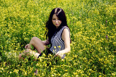 Happy woman sitting on yellow sunny flowers field Stock Image