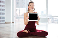 Happy woman sitting in yoga pose showing blank screen tablet Royalty Free Stock Photos