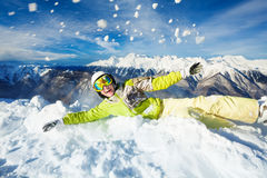 Happy woman in ski outfit throw snow up. Skier woman in mask and helmet through up snow over high mountains Royalty Free Stock Photos