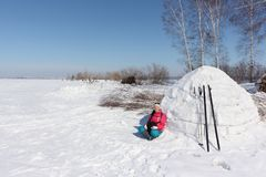 Happy woman skier in a red jacket sitting near an igloo. On a snowy glade, Siberia, Russia Stock Images